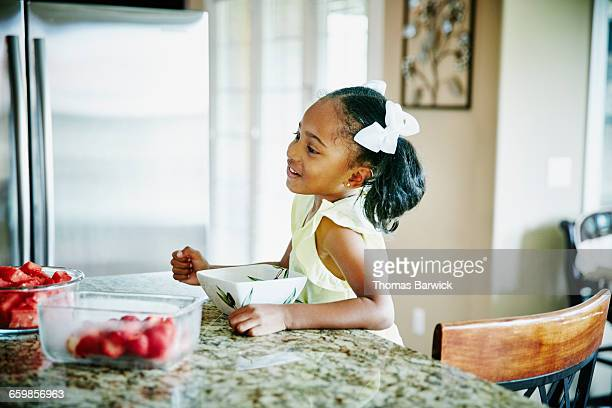 Young girl eating breakfast at kitchen counter