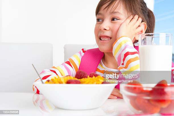 Young girl eating breakfast before heading to school