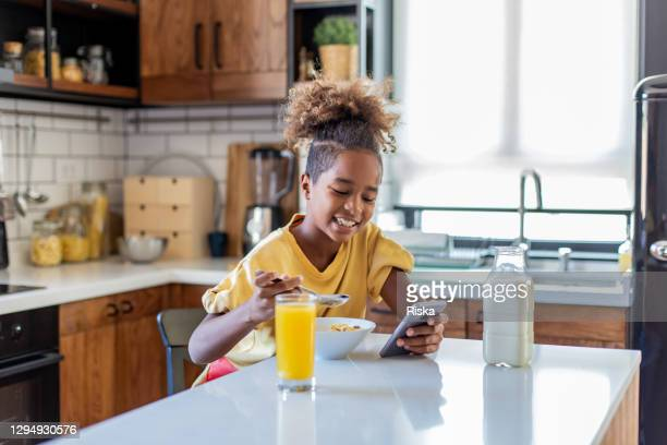 young girl eating breakfast in the morning - teenagers only stock pictures, royalty-free photos & images