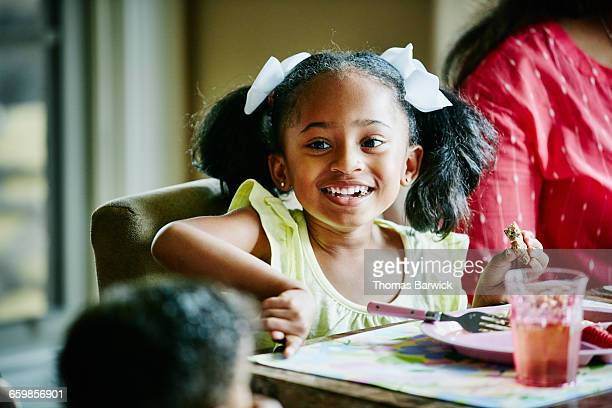 Young girl eating breakfast with family in home