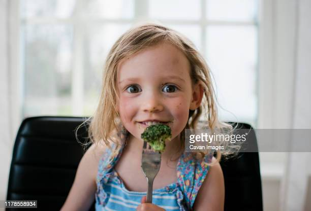young girl eating broccoli at home with a messy face - eating stock pictures, royalty-free photos & images