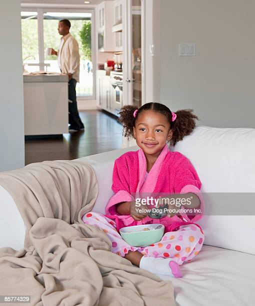 young girl eating cereal and watching tv - dog eats out girl stock pictures, royalty-free photos & images