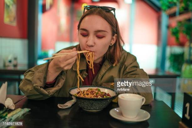 young girl eating chinese food in a restaurant in autumn - thai food stock pictures, royalty-free photos & images