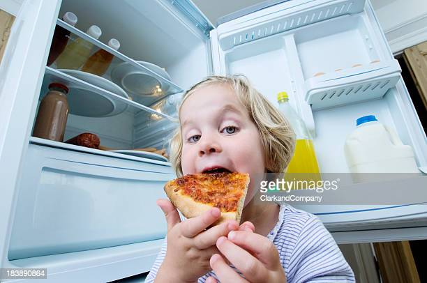 Young Girl Eating Cold Pizza From The Fridge
