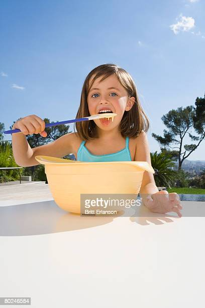 Young girl eating cream .