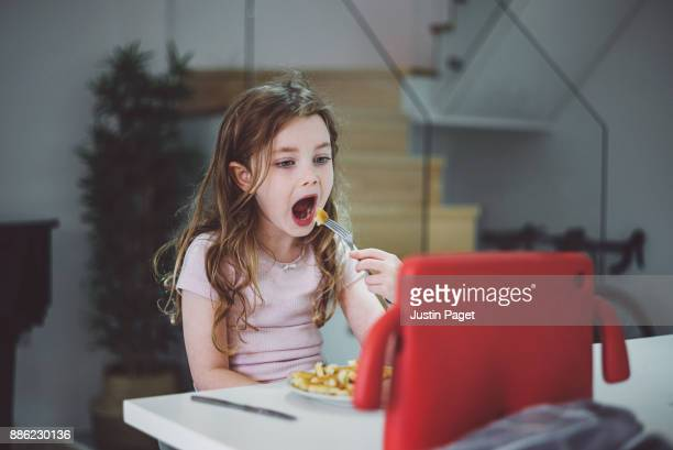 Young girl eating dinner watching tablet