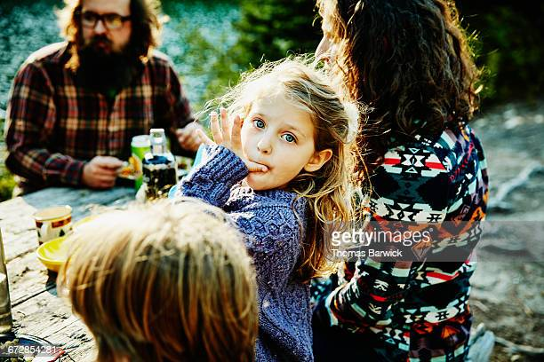 Young girl eating dinner with family while camping