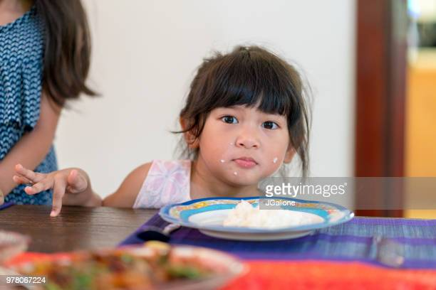 Young girl eating dinner with rice on her face