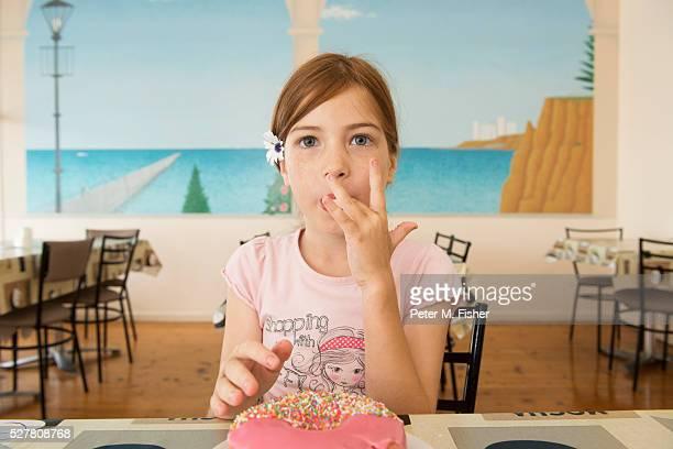 Young girl eating doughnut, Australia