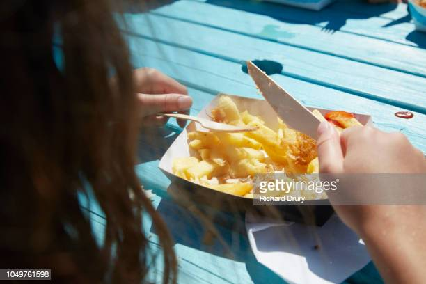 Young girl eating fish & chips at a beachside cafe