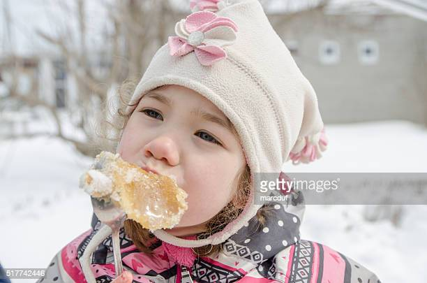 Young girl eating maple syrup taffy outside