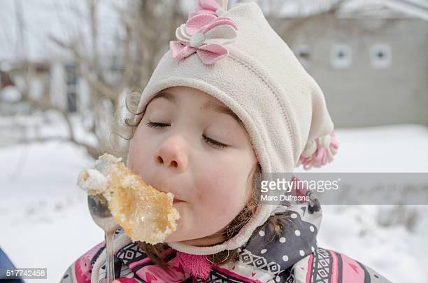 Junges Mädchen Essen Ahornsirup-Toffee außerhalb