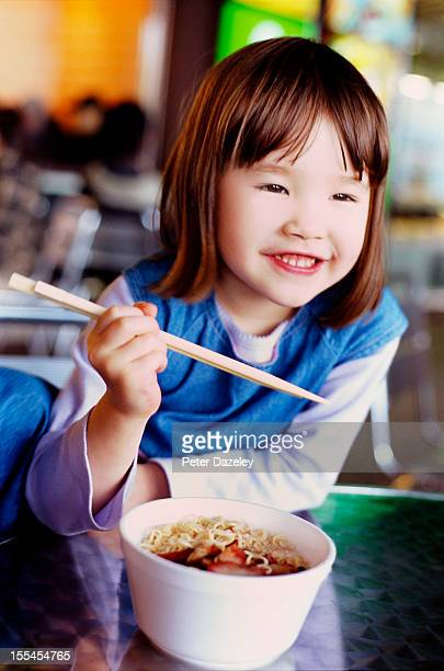 A young girl eating noodles with chopsticks
