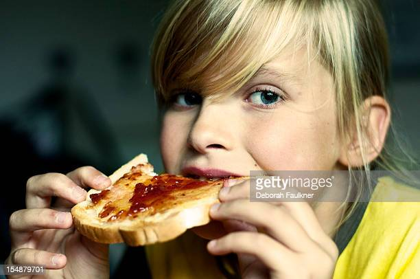 young girl eating toast with jam - bread stock pictures, royalty-free photos & images