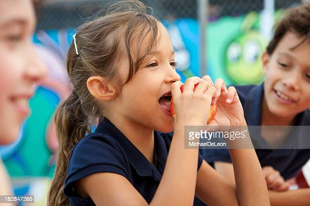 A young girl eats a fruit during lunch break at school