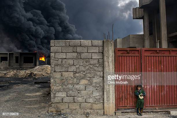 A young girl eats bread as she stands outside her home in front of a burning oil well set on fire by fleeing ISIS members on November 10 2016 in Al...