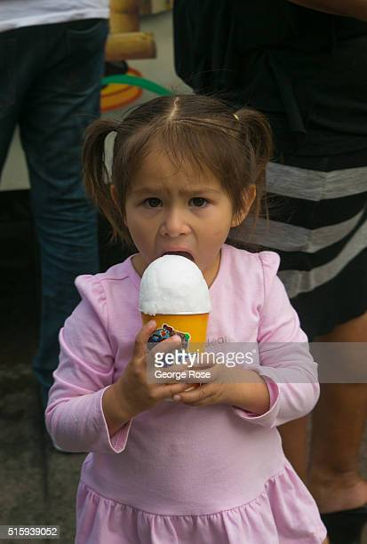 A young girl eats shaved ice outside the George R Brown Covention Center on February 28 2016 in Houston TX Despite the plunge in oil prices Houston...