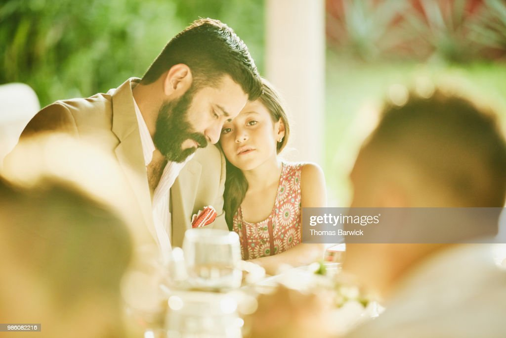 Young girl embracing father during outdoor wedding reception dinner : Stock Photo