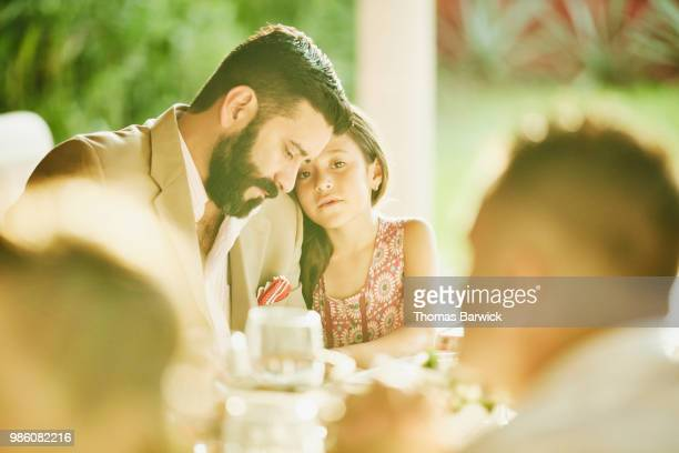 Young girl embracing father during outdoor wedding reception dinner