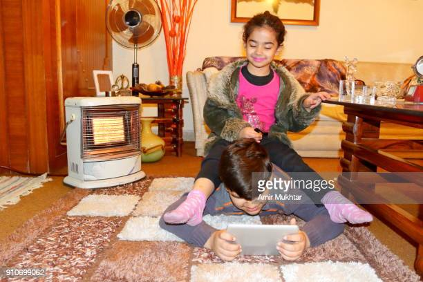 Young Girl Enjoying And Irritating Young Boy While Using Tablet