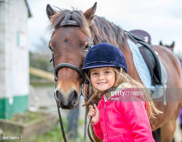 young girl enjoying horse riding lesson - horseback riding stock pictures, royalty-free photos & images