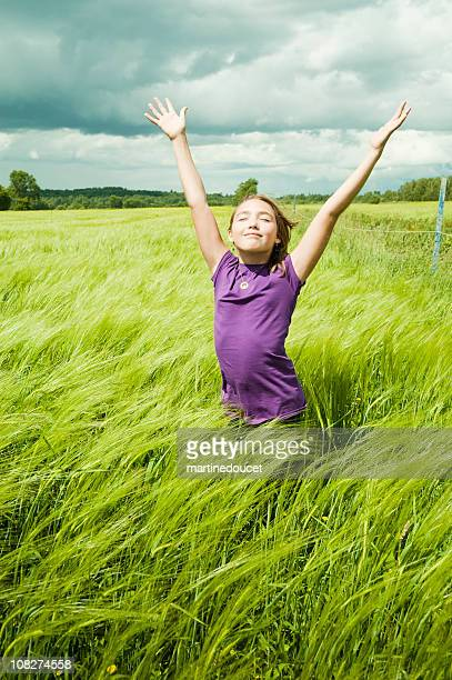 Young girl enjoying nature in windy wheat field in summer.
