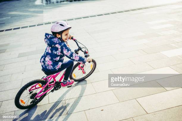 Young Girl Enjoying Riding Bicycle on Town Square