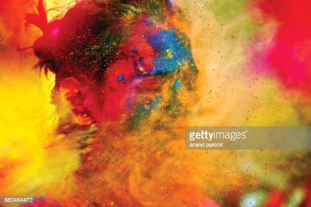 A Young girl enjoying shower of colours during Holi festival, India