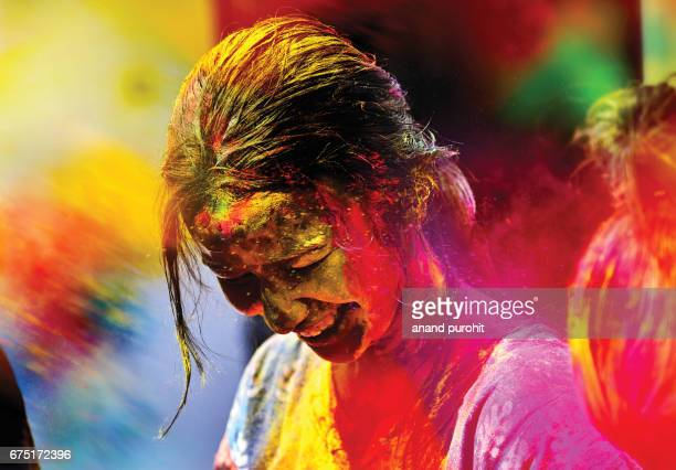 A young girl enjoying the holi festival with coloured powder exploding around face during the vibrant hindu festival, India