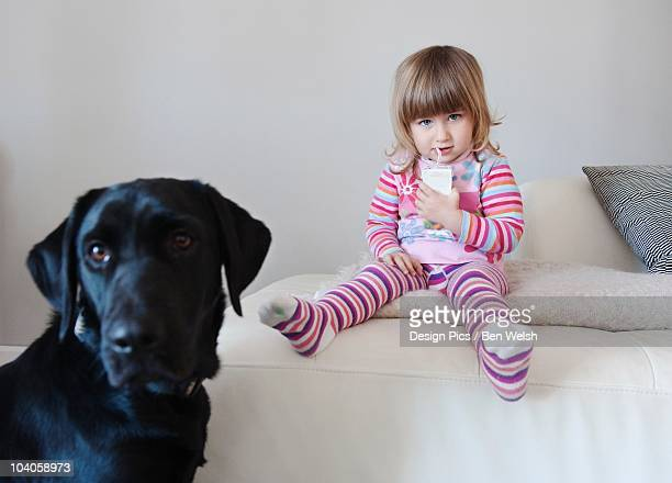 A Young Girl Enjoys A Juice Box While Sitting Beside Her Pet Dog