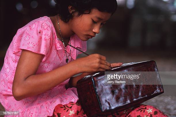 A young girl etches designs in lacquerware in the backroom of a large shop Children from a young age are often put to work in family businesses...