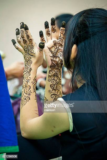 Young girl examinig mehndi tattoo on her hands.