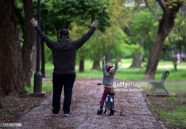 Young girl exercises beside a man in a park in Seville on April 26, 2020 amid a national lockdown to prevent the spread of the COVID-19 disease. -...