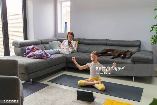 young girl exercising whilst mother works from home - abstand halten stock-fotos und bilder
