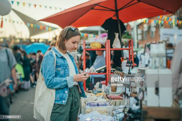 young girl exploring organic body care goods at an open-air market with zero waste concept - art and craft stock pictures, royalty-free photos & images