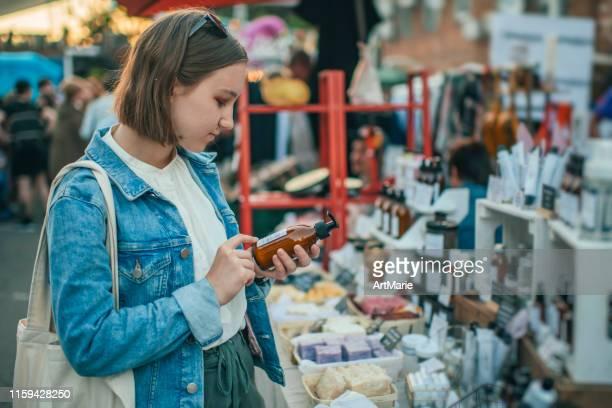 jovencita explorando productos orgánicos para el cuidado del cuerpo en un mercado al aire libre con concepto de residuos cero - cuidado del cuerpo fotografías e imágenes de stock