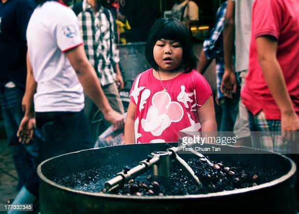 Young girl fascinated by the spinning roasted chestnuts in Petaling Street, Kuala Lumpur.