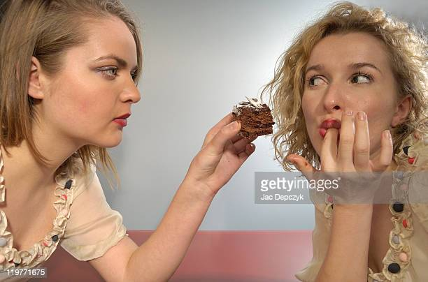 Young girl feeding chocolate cake to her friend.