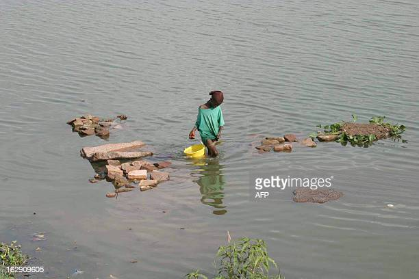 A young girl fetches water from the Niger river 14 June 2005 in Bamako Mali is among the world's poorest countries and faces a food shortage this...