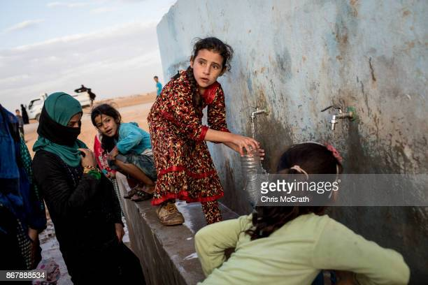 A young girl fills a bottle at a water pump station at a camp for internally displaced people on October 29 2017 in Ain Issa Syria Following three...