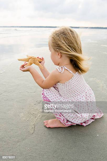 young girl finds starfish on beach - hilton head stock pictures, royalty-free photos & images
