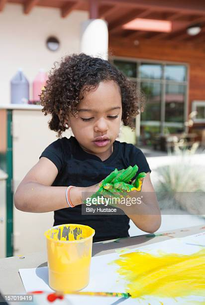 Young girl (age 3-4) finger painting at school
