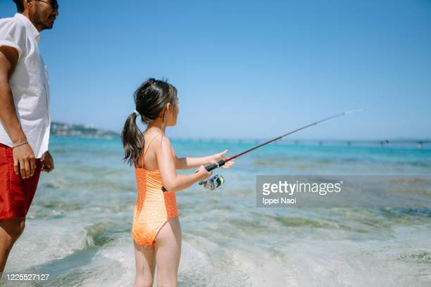 young girl fishing from beach, okinawa, japan - ippei naoi stock pictures, royalty-free photos & images