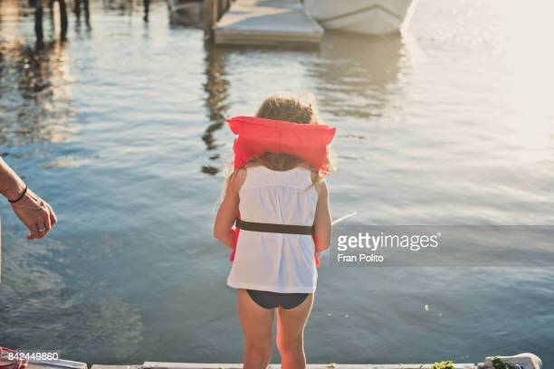 A young girl fishing on a pier in the summer.