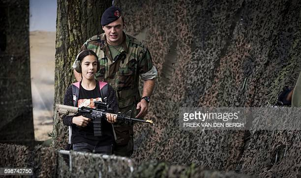 Young girl flanked by a Dutch soldier participate in the 39th edition of the World Port Days on September 2, 2016 in the port of Rotterdam. / AFP /...
