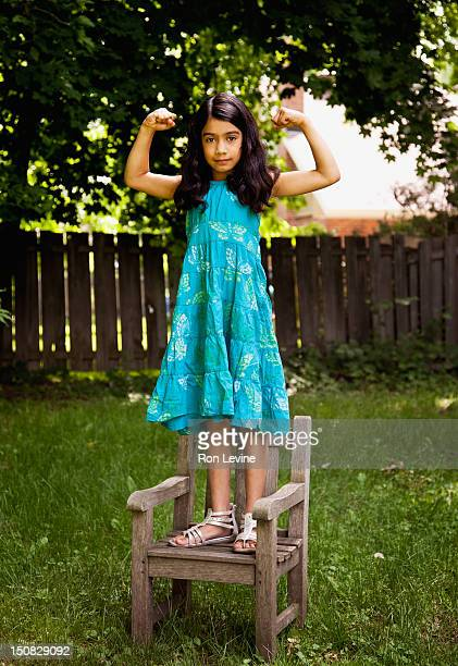Young girl flexing muscles while standing on chair
