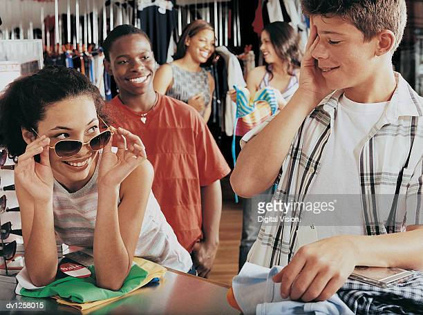 Young Girl Flirting With a Shy Young Boy at the Checkout Counter of a Clothes Shop