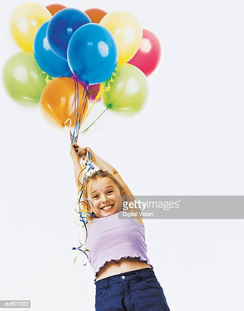Young Girl Floating by Holding a Large Group of Multi Coloured Balloons