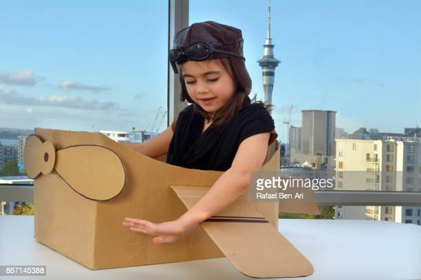 young girl flying a cardboard airplane above city - rafael ben ari stock pictures, royalty-free photos & images