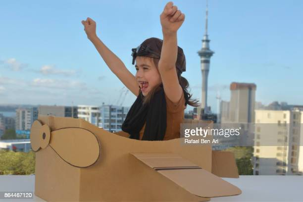 Young girl flying a cardboard airplane above city
